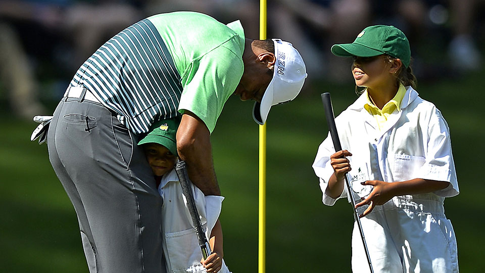 Tiger Woods hugs his son Charlie as daughter Sam looks on following a putt on the ninth green during the 2015 Masters Par 3 contest.