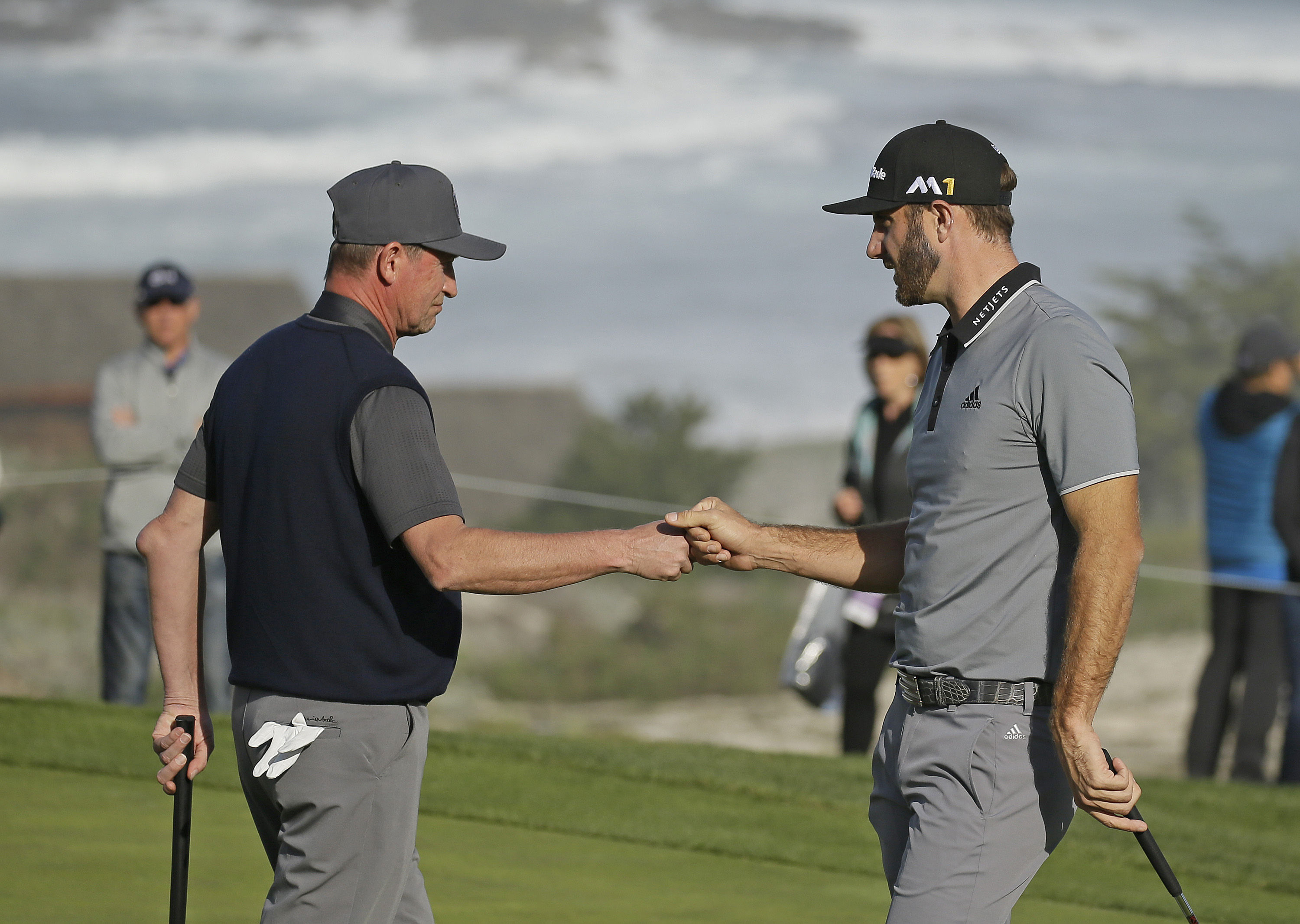 Wayne Gretzky, left, is greeted by playing partner Dustin Johnson, right, after putting on the second green of the Spyglass Hill Golf Course during the first round of the AT&T Pebble Beach National Pro-Am golf tournament Thursday, Feb. 11, 2016, in