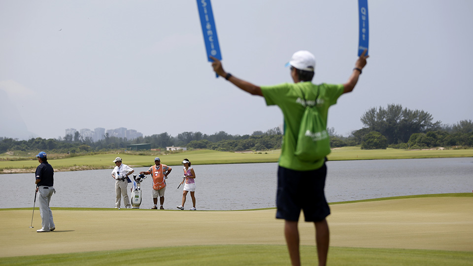 A golf marshall holds up quiet signs during the 2016 Aquece Rio Golf Challenge at the Olympic Golf Course in Rio de Janeiro, Brazil, Tuesday, March 8, 2016.