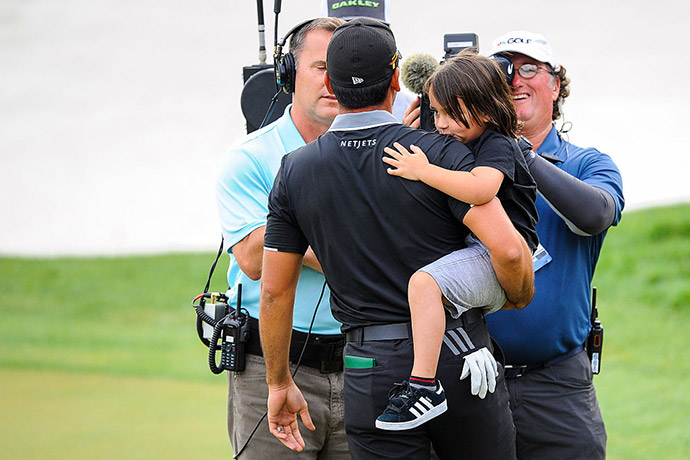 Jason Day of Australia is kissed on the shoulder by his son Dash following his one stroke victory on the 18th hole green during the final round of the Arnold Palmer Invitational presented by MasterCard at Bay Hill Club and Lodge.