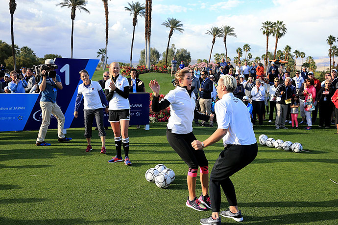 Paula Creamer of the United States is welcomed to the first tee by Abby Wambach of the United States soccer team during the ANA Footgolf Faceoff between Team USA and Team Japan