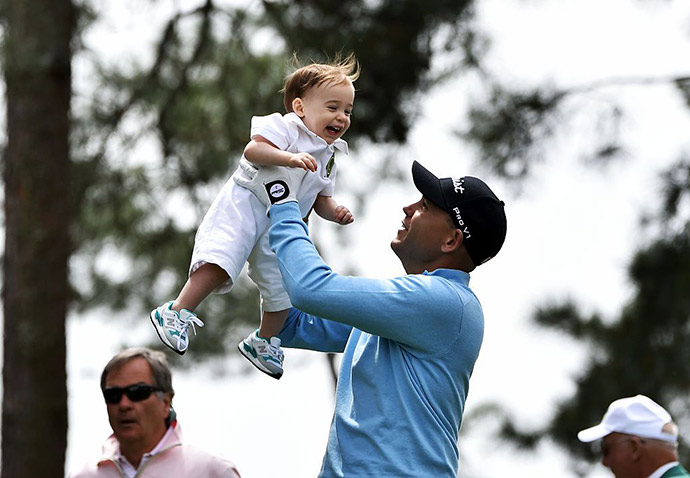 US golfer Bill Haas playfully tosses his son in the air during the Par 3 contest.