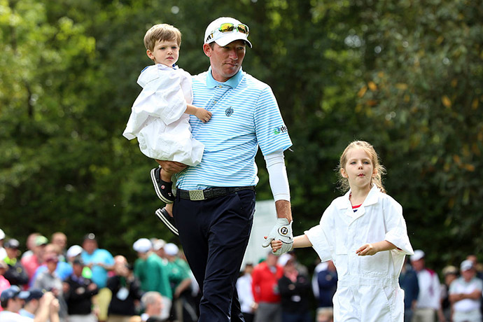 Jim Herman of the United States and children walk during the Par 3 Contest.