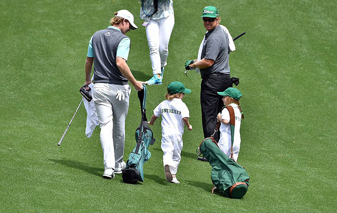 US golfer Brandt Snedeker (L) walks with his son Austin during the Par 3 contest.