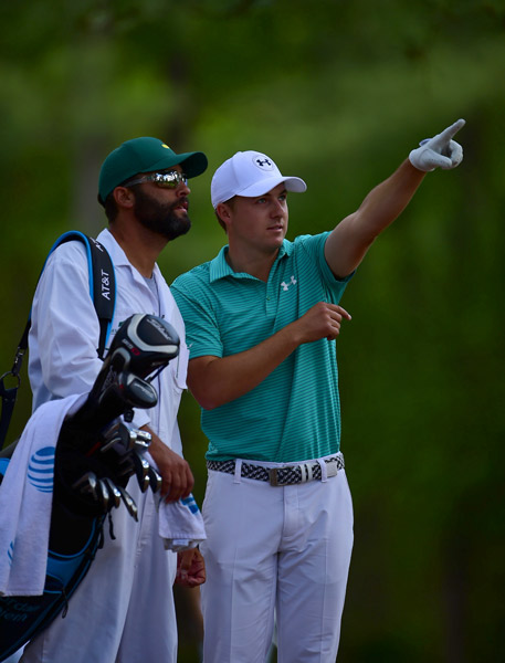 Spieth and caddie Michael Greller discuss a shot during round 1.