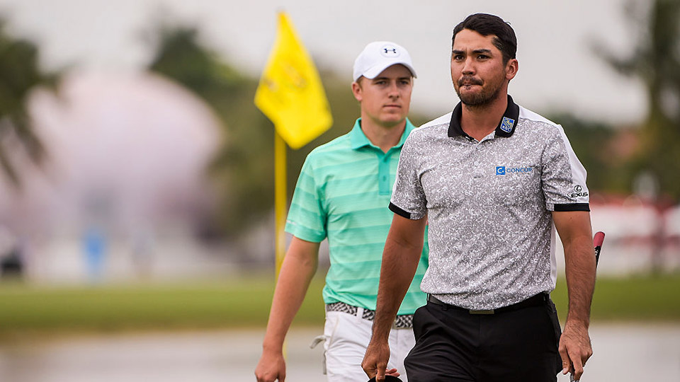 Jason Day of Australia walks in front of Jordan Spieth on the 18th hole green during the first round of the World Golf Championships-Cadillac Championship.