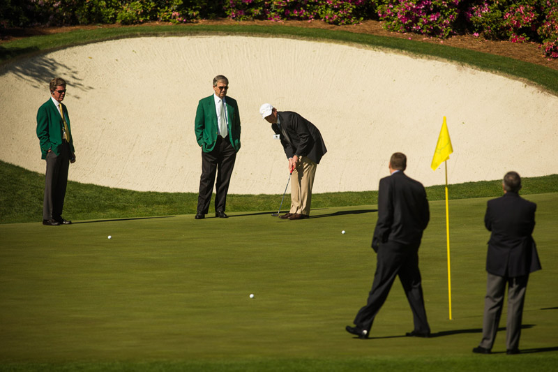 Tournament officials putt to Friday's hole location at the 13th green prior to the second round.