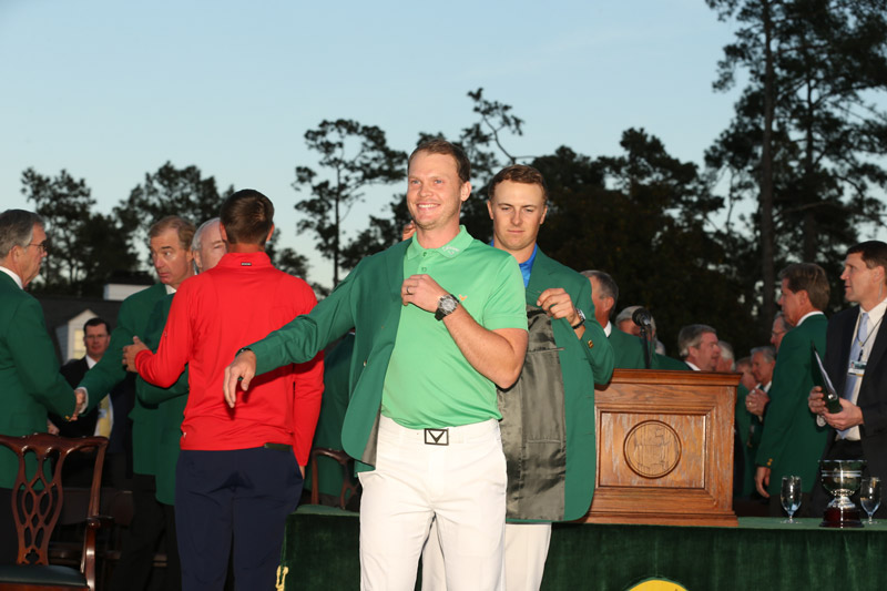 Spieth, last year's Masters champion, puts the green jacket on Willett.