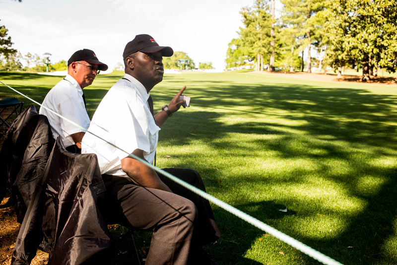 Security guard Willy Powell also helps gallery guards follow the flight of tee shots at the 18th hole during the final round.