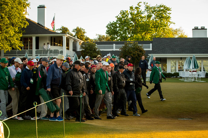 Early Sunday morning, members and security personnel lead the first patrons through the gates and on to the area surrounding the 18th green to reserve spots to view the final hole of the 2016 Masters.