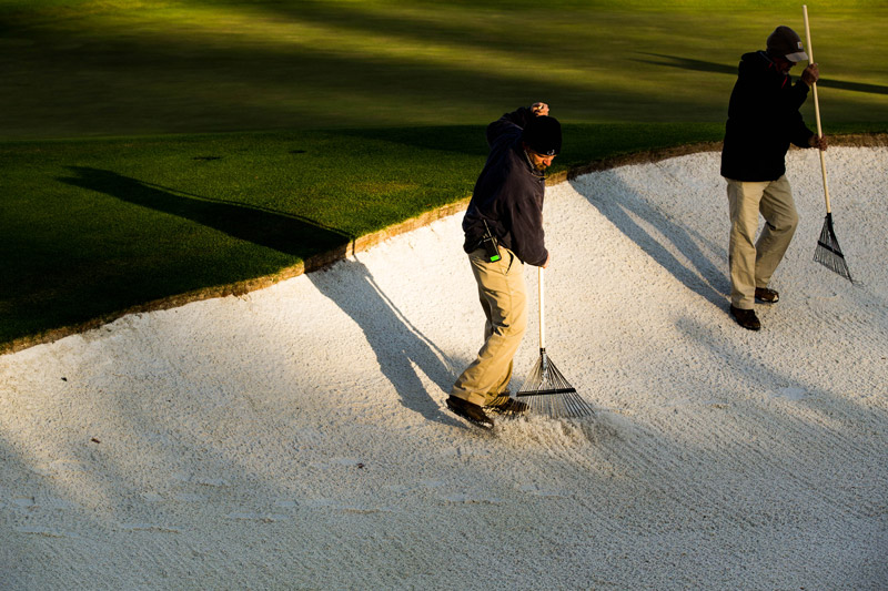Members of the grounds staff rake a bunker at the 18th hole in preparation for the final round.