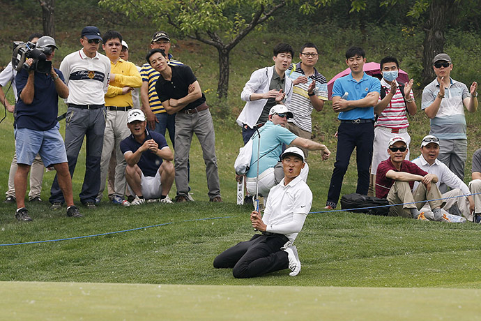 Li Haotong of China celebrates after he plays a shot during the final round of the Volvo China open at Topwin Golf and Country Club