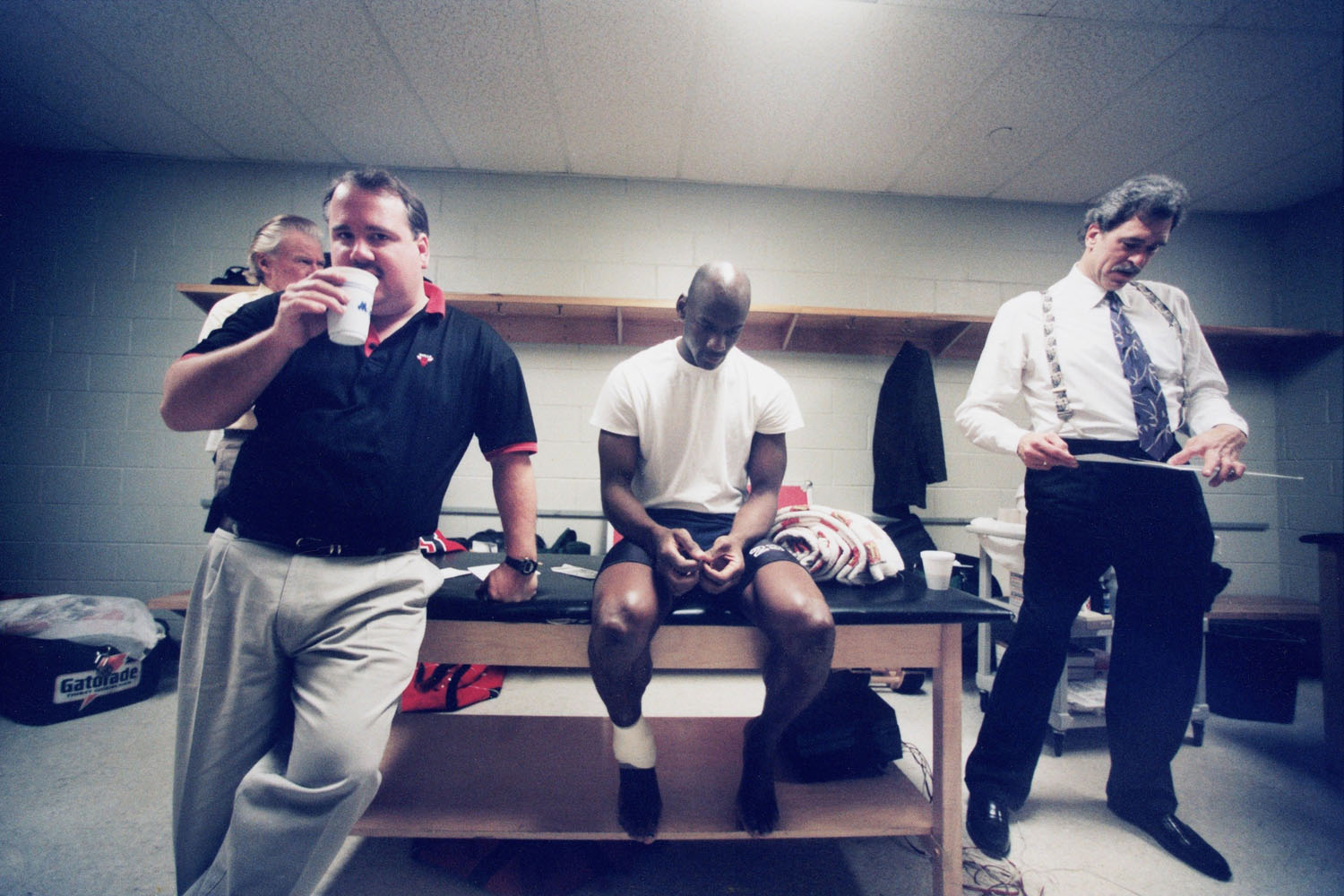 Michael Jordan along with head coach Phil Jackson with the Bulls' trainer in locker room in 1993.
