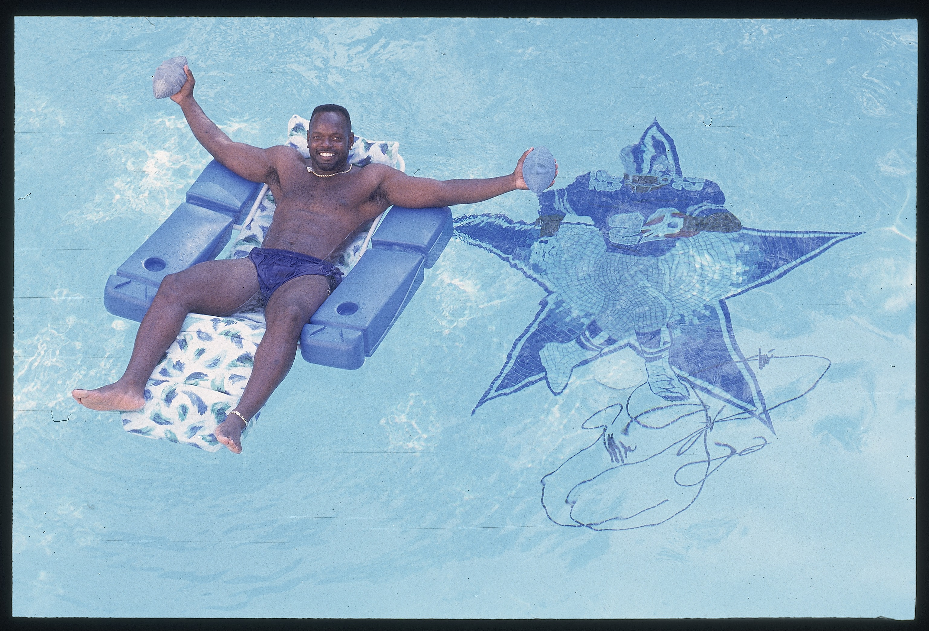 Emmitt Smith of the Dallas Cowboys relaxing on chair in the pool at his home in Dallas, Texas in 1996.