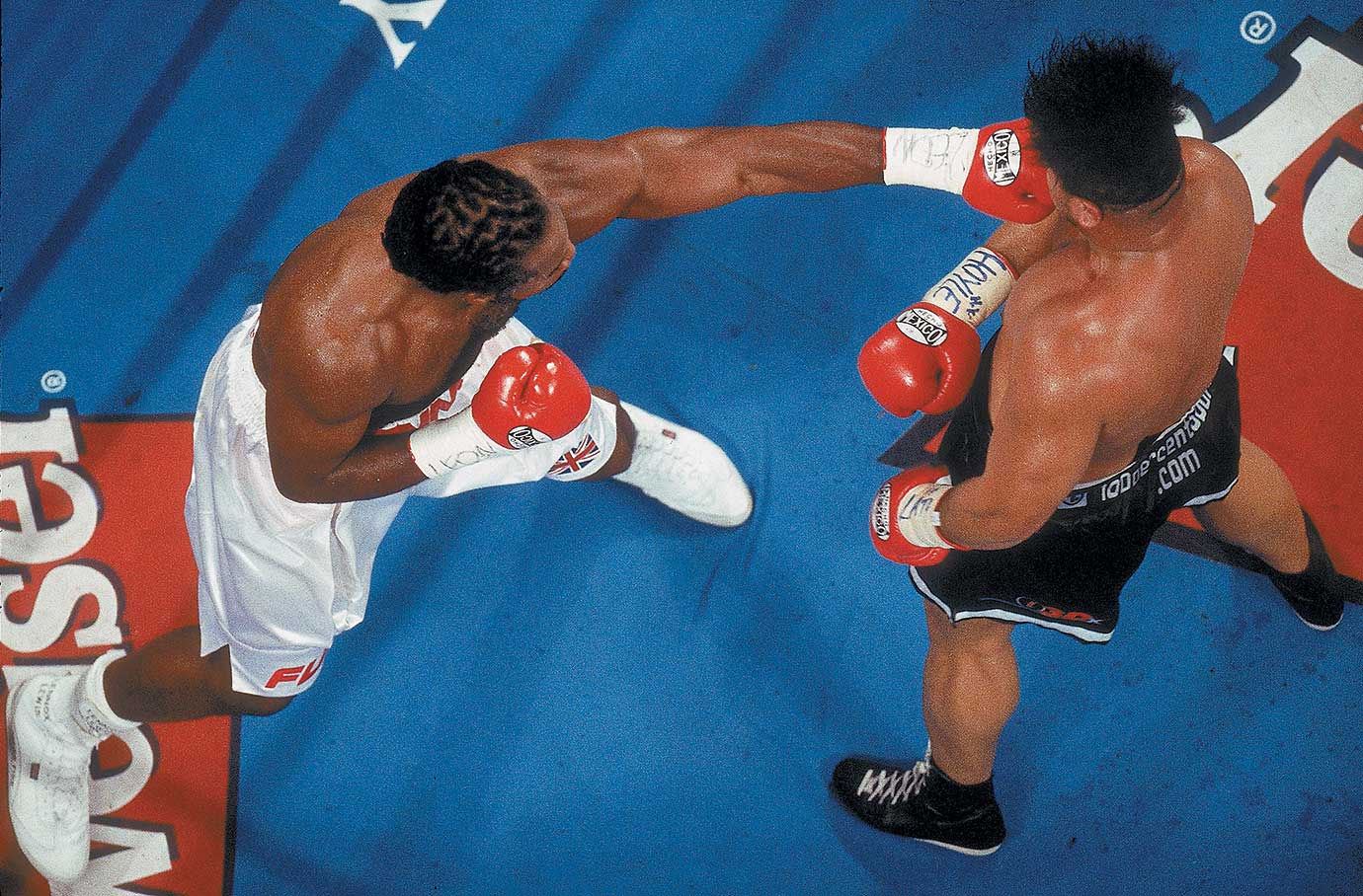 Lennox Lewis lands a left to the head of David Tua during 2000 heavyweight championship bout in Las Vegas.