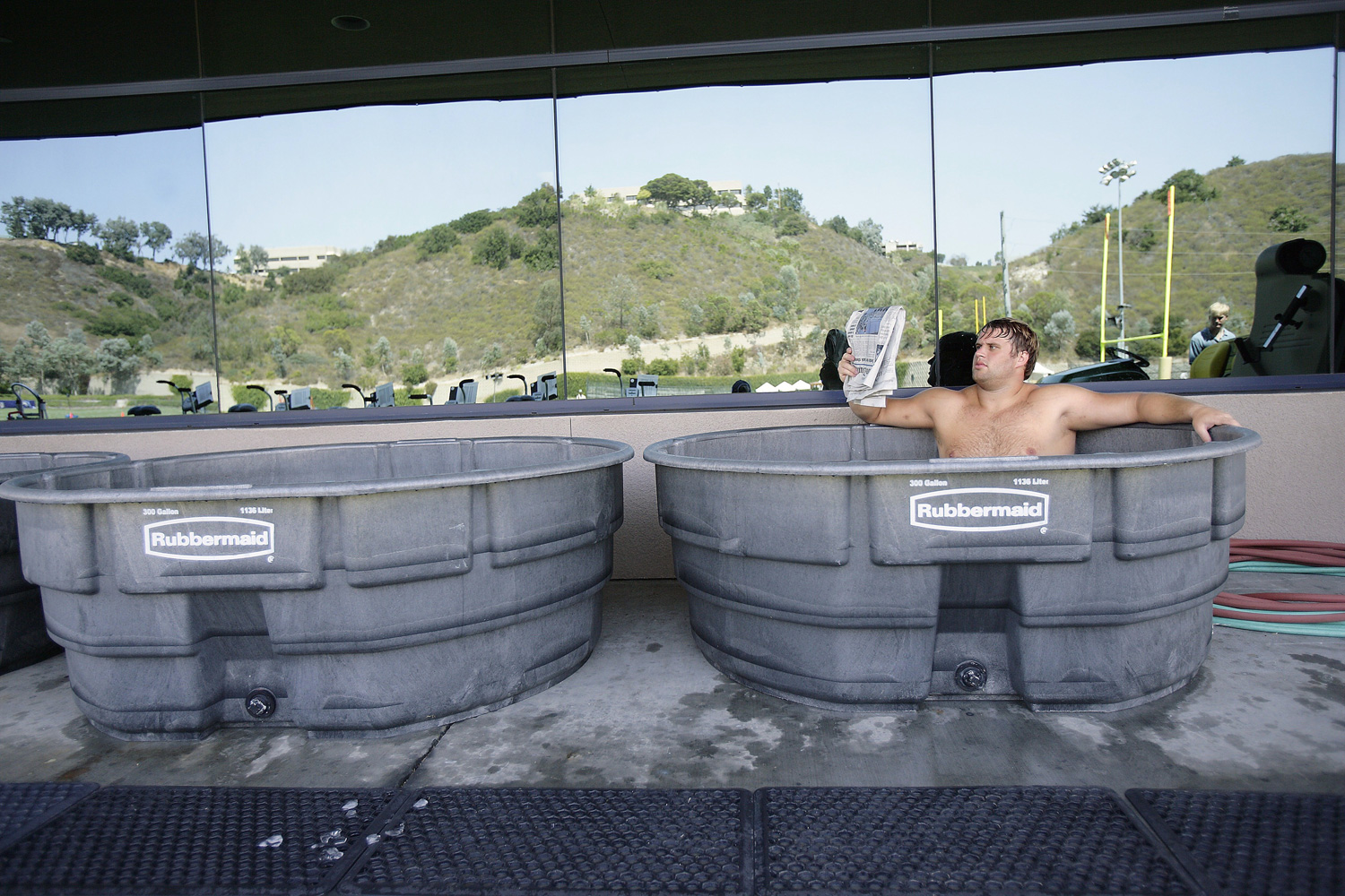 Former San Diego Chargers offensive tackle Wesley Britt hangs out reading the newspaper in giant ice-filled tub during training camp in July 2005.