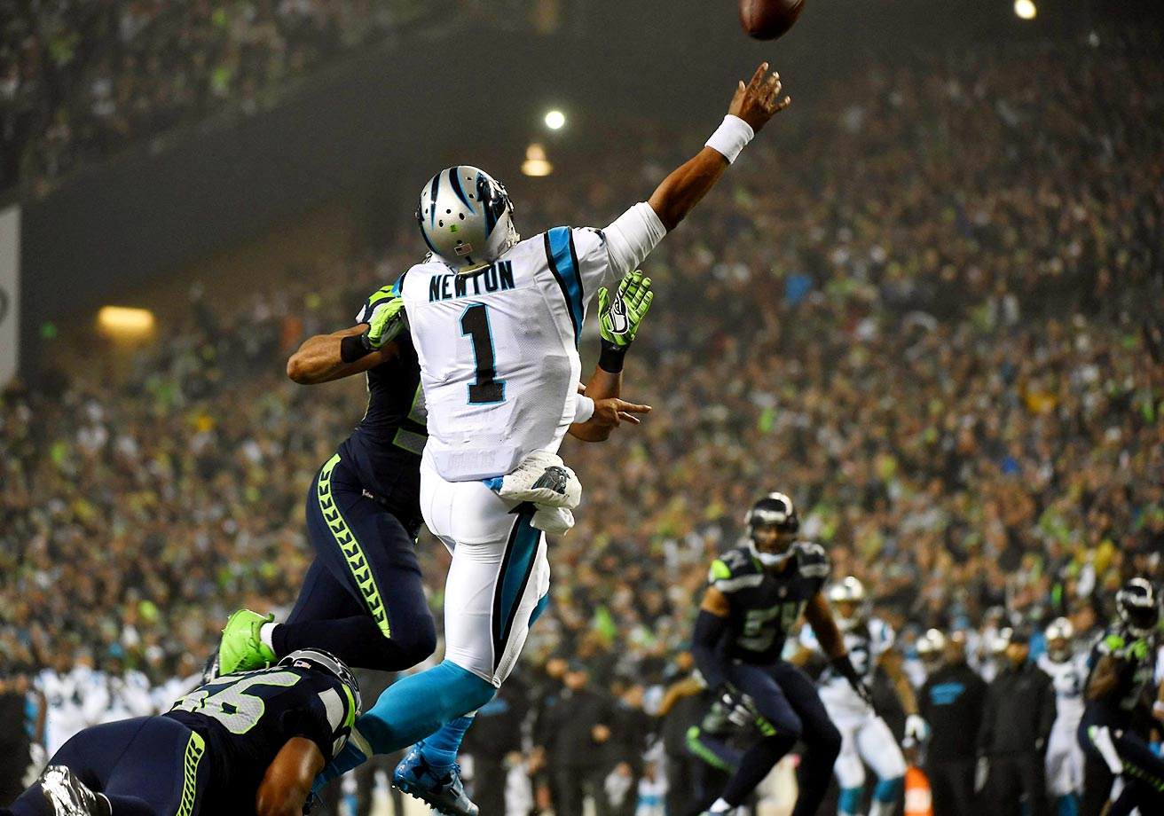 Cam Newton throws a pass over Seattle Seahawks defensive end Cliff Avril during the 2014 NFC divisional playoffs in Seattle. The Seahawks went on to win 31-17 en route to their second straight Super Bowl appearance.                                                                                             Text credit: Daniel Hersh