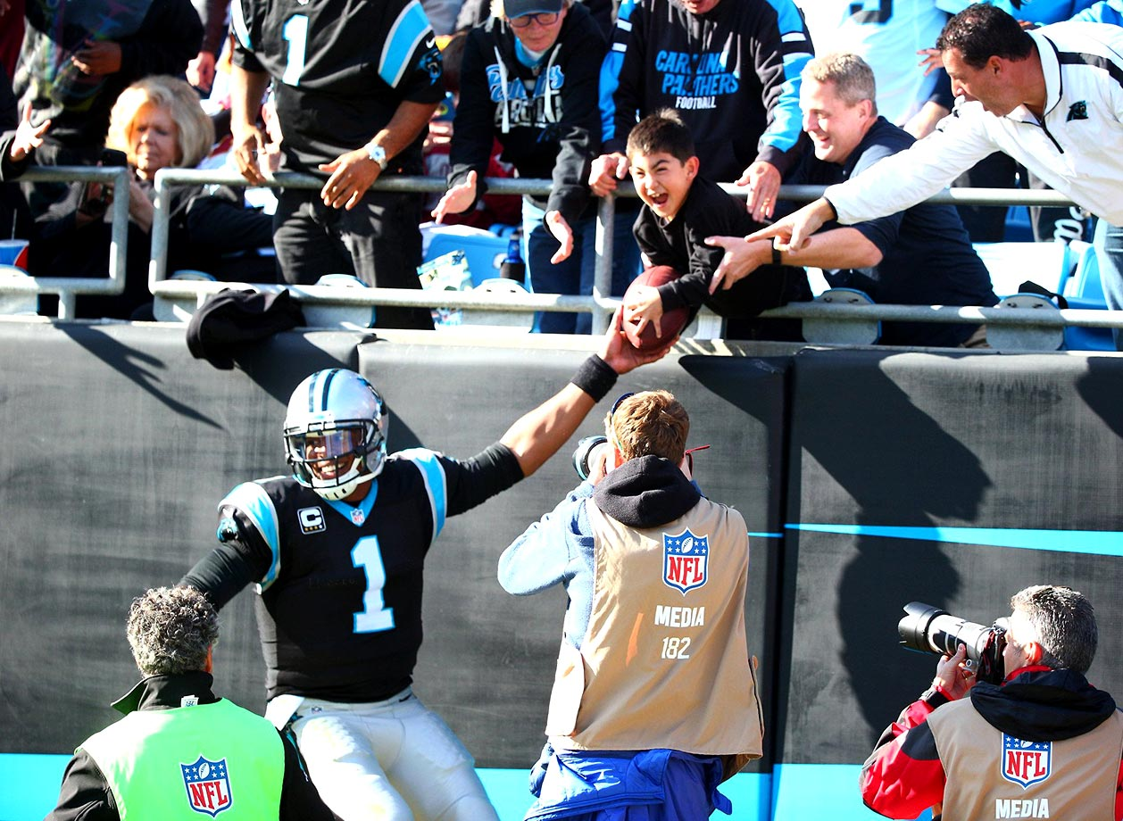 As is his custom, Cam Newton gives a ball to a young fan after a Carolina touchdown.                                                               Text credit: Daniel Hersh