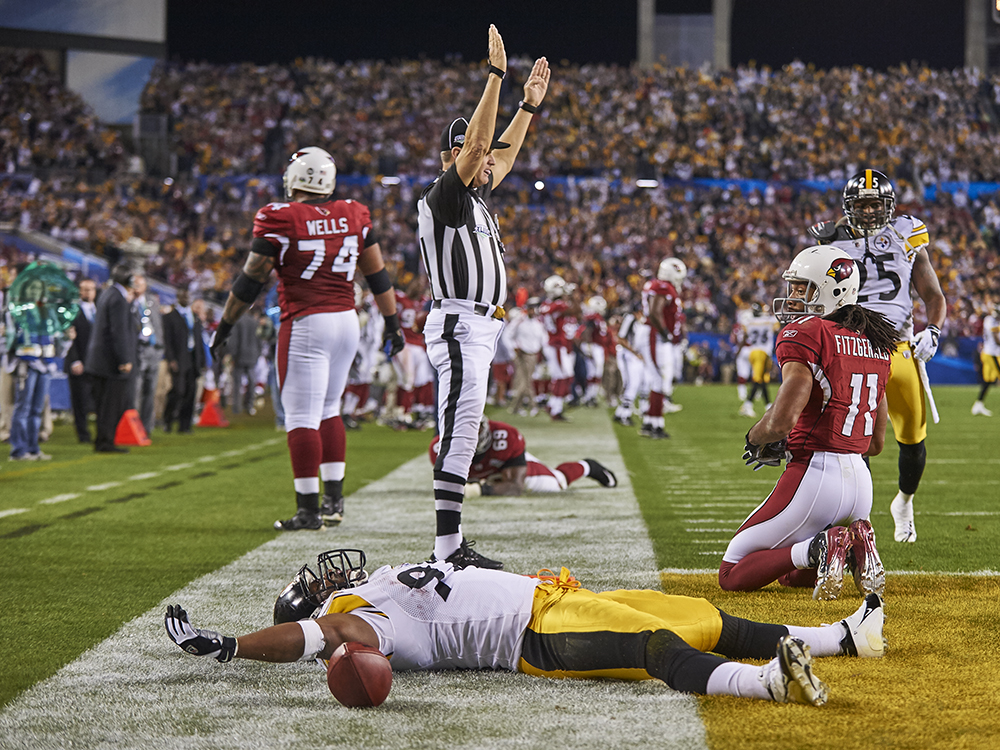 "On the last play of the first half, Pittsburgh's James Harrison took everyone's breath away — including his own. The Steelers had a 10-7 lead on Arizona, but the Cardinals had the ball at the Pittsburgh two-yard line with 18 seconds left and looked ready to take a halftime lead. Quarterback Kurt Warner tried to hit wide receiver Anquan Boldin on a slant pattern, but Harrison jumped in front of Boldin, snagged the ball, and bulldozed his way down the sideline. One hundred yards later, he collapsed in the end zone. ""I've never been more emotionally drained in my life,"" he said. He was also drained of oxygen. Once he was back on the Steelers' bench, he received an oxygen mask to help him breathe. Harrison didn't mind the long-distance sprint, though, considering the Steelers won 27-23."