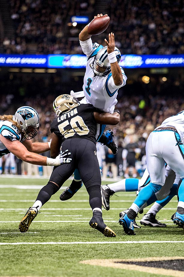 Cam Newton leaps over Saints linebacker Curtis Lofton for a touchdown. In addition to three passing touchdowns, Newton had 83 yards rushing and one touchdown run during the game.                                                              Text credit: Daniel Hersh
