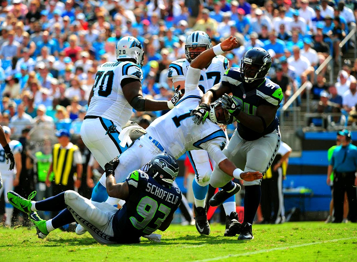 Cam Newton leaps through New Orleans Saints defenders during a December 2013 game at Bank of America Stadium. The Panthers defeated the Saints 17-13 to take sole possession of the NFC South heading into the last game of the season.                               Text credit: Daniel Hersh