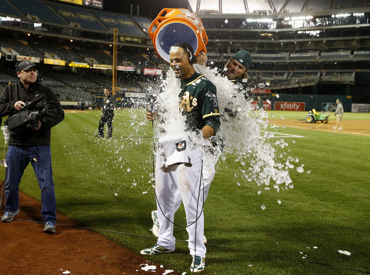 Coco Crisp is doused by teammate Josh Reddick after hitting a walk-off home run in the 12th inning of the A's 3-2 win over the Mariners.