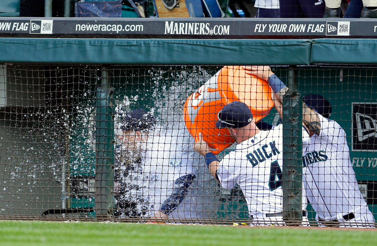 Kyle Seager is doused by teammates John Buck and Stefen Romero following the Mariners a 6-5 win over the Rangers. Seager hit a pair of homers, including a three-run shot in the eighth, to lead the Mariners to a comeback win.