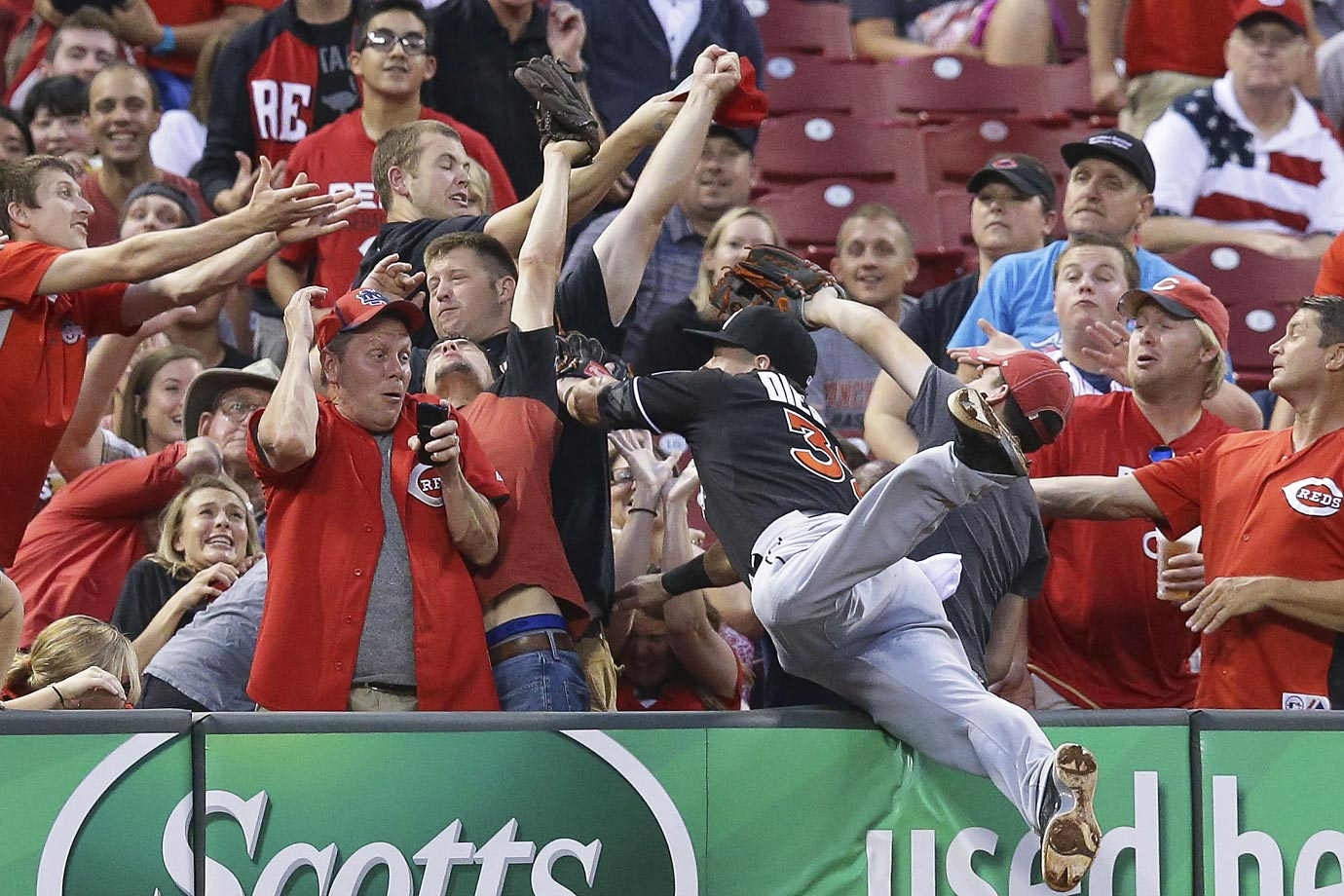 Derek Dietrich of the Marlins dives into the stands for a foul ball against the Cincinnati Reds.