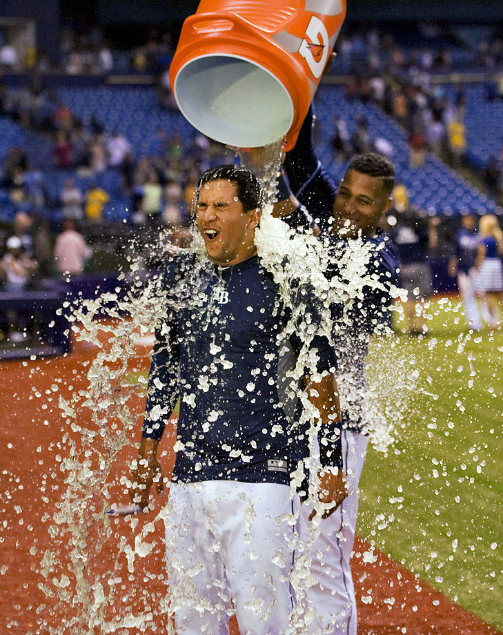 Cole Figueroa is doused by teammate Yunel Escoba after his pinch-hit, run-scoring double in the bottom of the ninth inning gave the Rays a 1-0 win over the Red Sox.