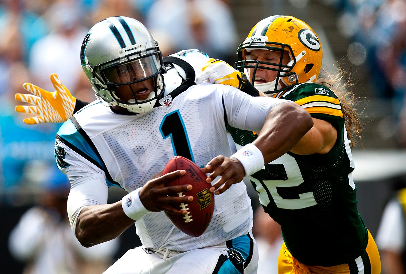 Cam Newton fights off Green Bay Packers cornerback Morgan Burnett to gain extra yardage during a September 2011 matchup. The Packers won 30-23 in Newton's second professional game. Text credit: Daniel Hersh