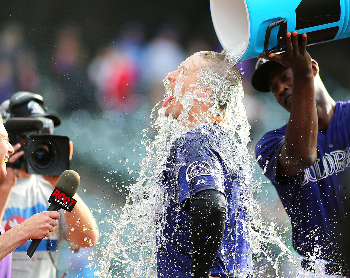 Brandon Barnes is doused by teammate LaTroy Hawkins after hitting a game-winning RBI triple in the bottom of the 10th inning of the Rockies 5-4 win over the Dodgers.