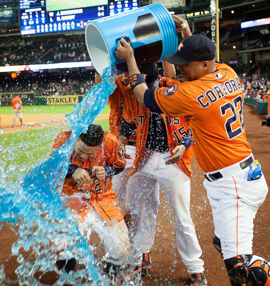 Jose Altuve (27) and Jason Castro (15) are doused by teammate Carlos Corporan after Castro hit a walk-off home run in the 11th inning of the Astros 4-3 win over the Tigers. Altuve had four hits, an RBI and two steals, including one of home in the game.
