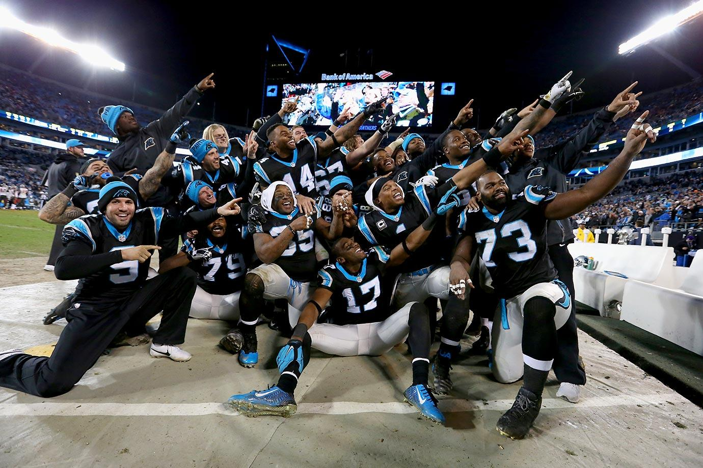 Cam Newton smiles with teammates during a photo he organized in the bench area during a game against Tampa Bay.  The Panthers won to clinch home field advantage throughout the playoffs.                                                              Text credit: Daniel Hersh