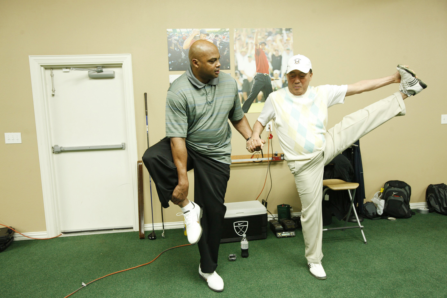 NBA on TNT announcer and former NBA basketball player Charles Barkley stretching with golf instructor Suckki Jang during taping for the Golf Channel's reality TV show The Haney Project at Hank Haney Golf Ranch at Vista Ridge.
