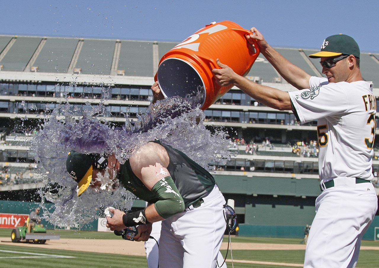 Jed Lowrie is doused by teammate Nate Freiman after his walk-off single in the A's 4-3 win over the Astros.