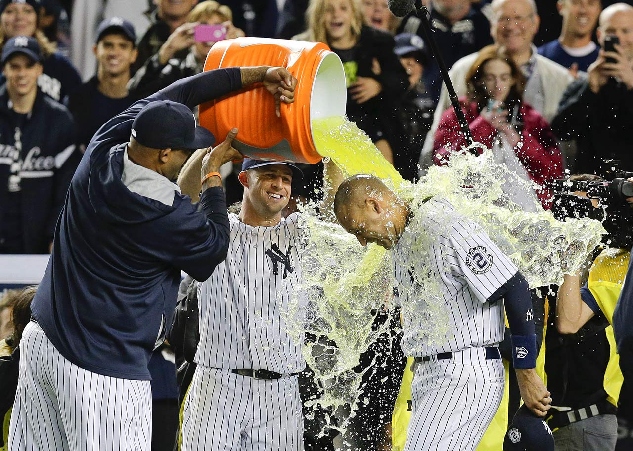Derek Jeter is doused by teammates C.C. Sabathia and Brett Gardner after his game-winning RBI single in the Yankees 6-5 win over the Orioles in Jeter's last home game.