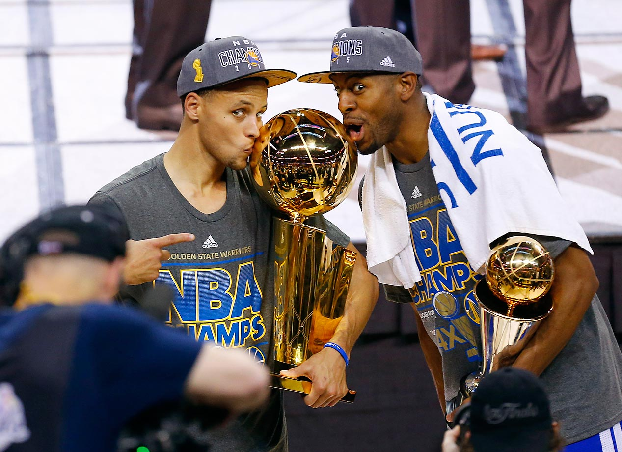 Stephen Curry and Andre Iguodala of the Warriors hold their trophies after winning the NBA Finals.