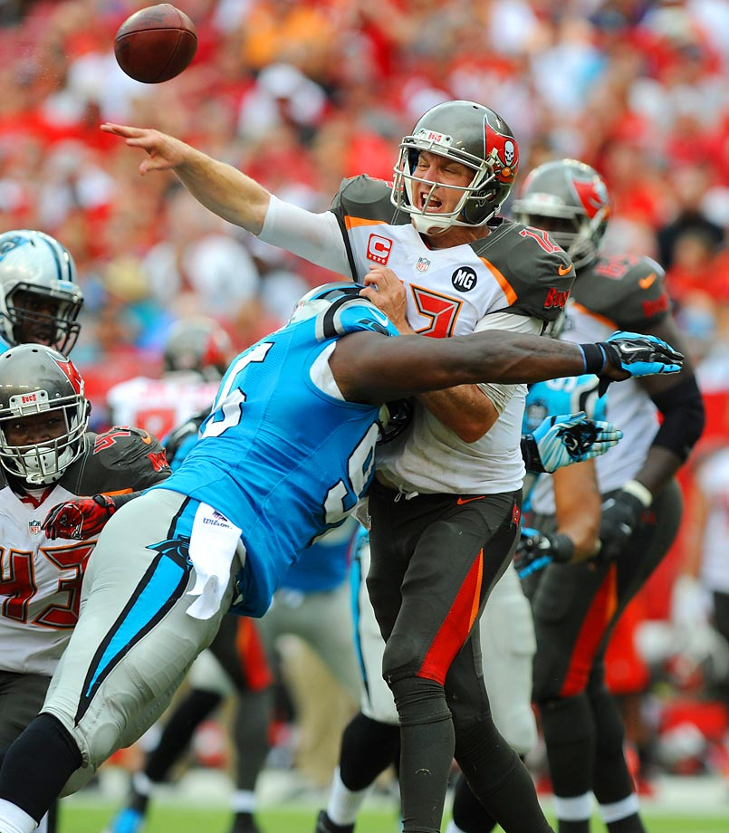 Tampa Bay Buccaneers quarterback Josh McCown throws an interception after being hit by defensive end Charles Johnson of the Carolina Panthers.