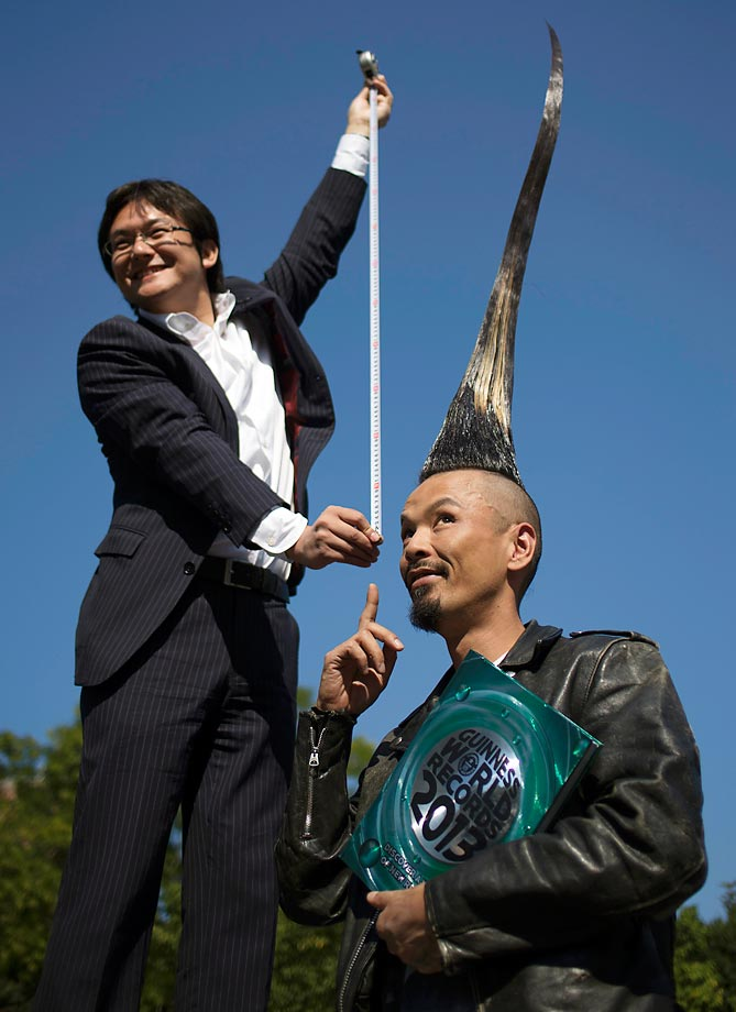 "Television journalist Takashi Yanagisawa holds a measuring tape from atop a step ladder while interviewing Japanese fashion designer Kazuhiro Watanabe, who holds the world record for the ""Tallest Mohawk."" According to the Guinness World Records, Watanabe's do stands at 3 feet 8.6 inches."