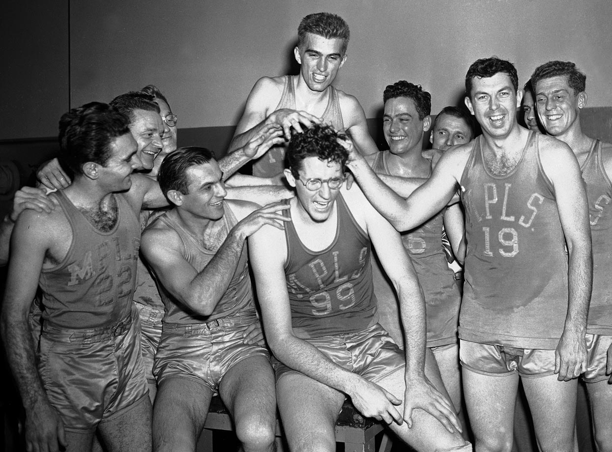 Lakers center George Mikan (99) gets his hair mussed by teammates after leading Minneapolis to its first-ever championship. Mikan set a Madison Square Garden scoring record with 48 points in a 101-74 victory over the Knickerbockers. The Lakers' 101 points also set an all-time team high scoring mark at the Garden.