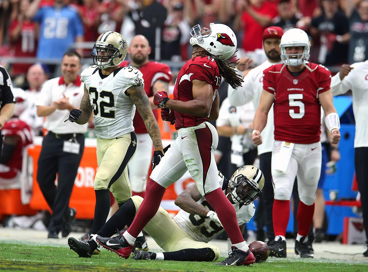 Wide receiver Larry Fitzgerald of the Arizona Cardinals celebrates a catch and run after dragging three New Orleans Saints defenders for extra yardage.