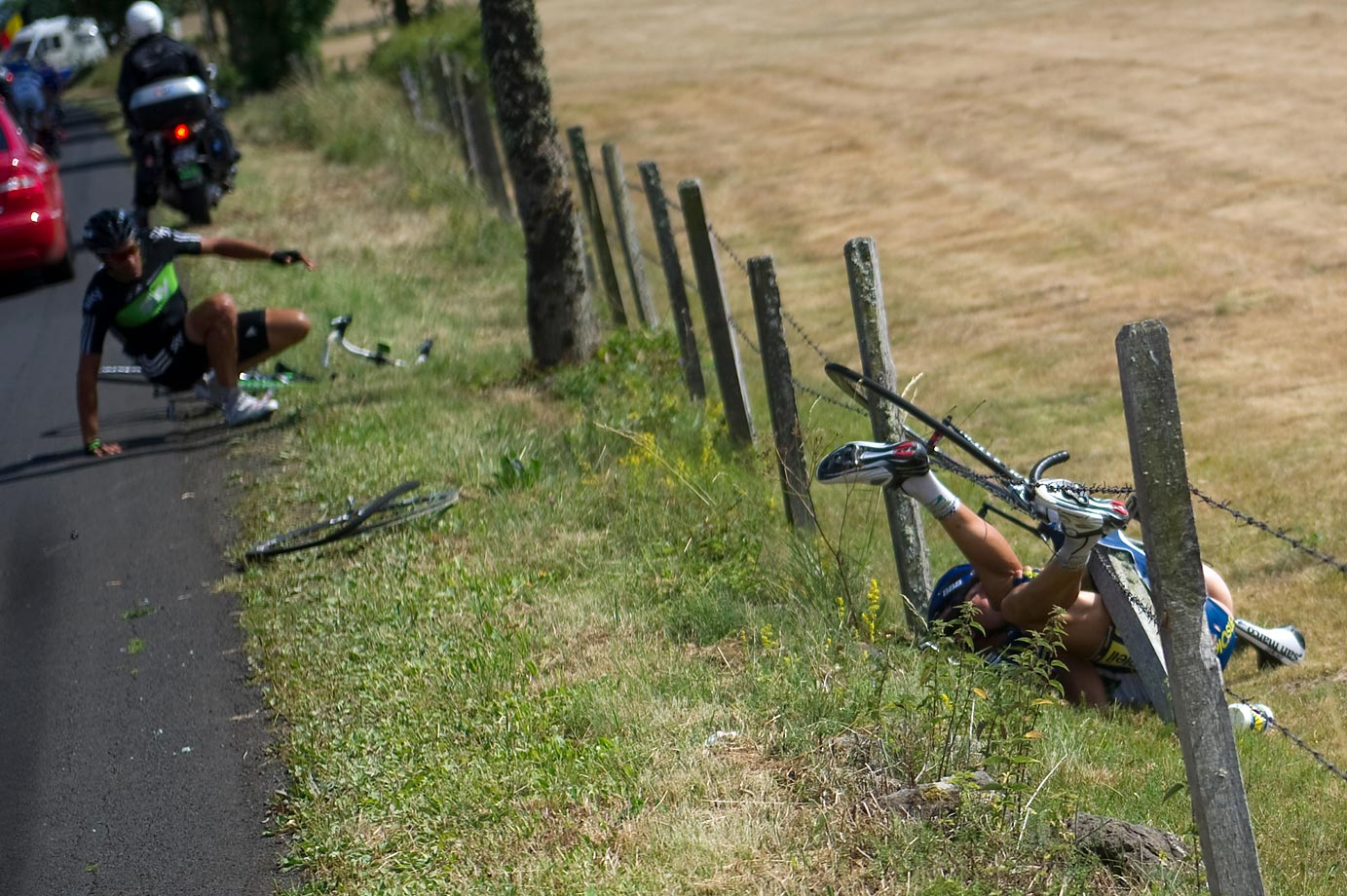 "Juan Antonio Flecha (left) and Johnny Hoogerland (entangled in fence) were run off the road by a shockingly reckless driver in stage 9 of the 2011 Tour.  Hoogerland went flipping into a barbed wire, suffering deep cuts that would take 33 stitches to close. Incredibly, he and Flecha both finished the stage, and were jointly awarded the Tour's ""Combativity Award"" for the day. The driver of the car, belonging to France Television 2/3, was expelled from the race."