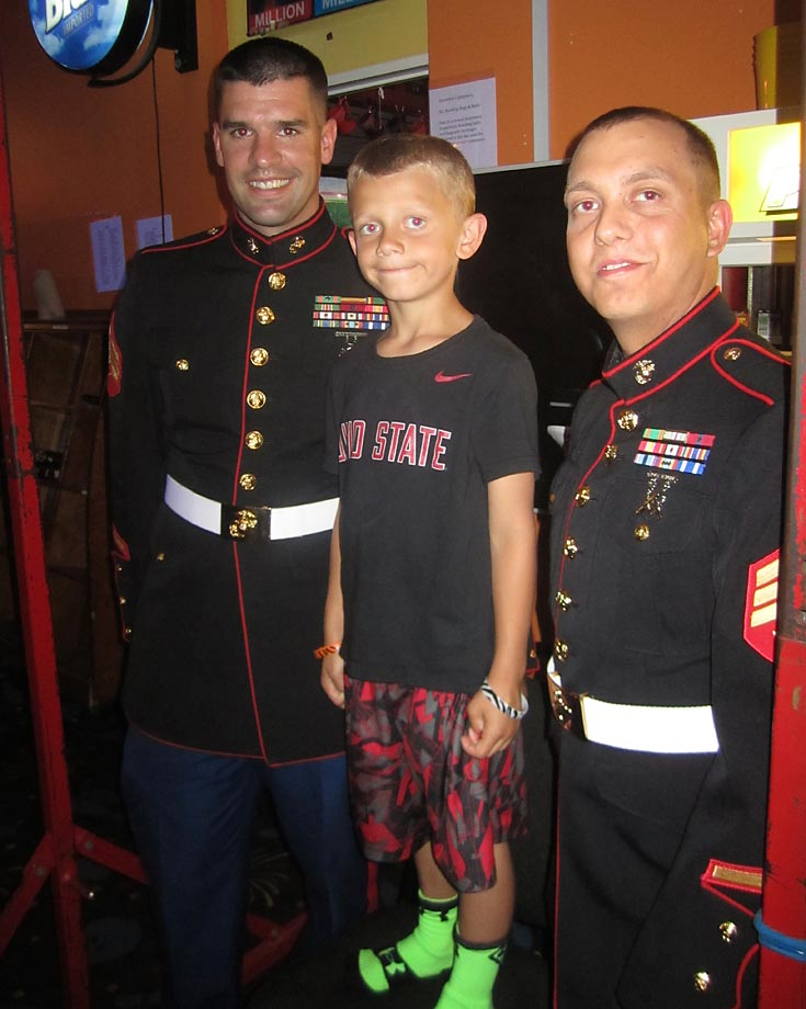 Sgt. Scott Sowers (left) and Sgt. William Payton of the U.S. Marine Corps smile with one of the littlest fans at the event.