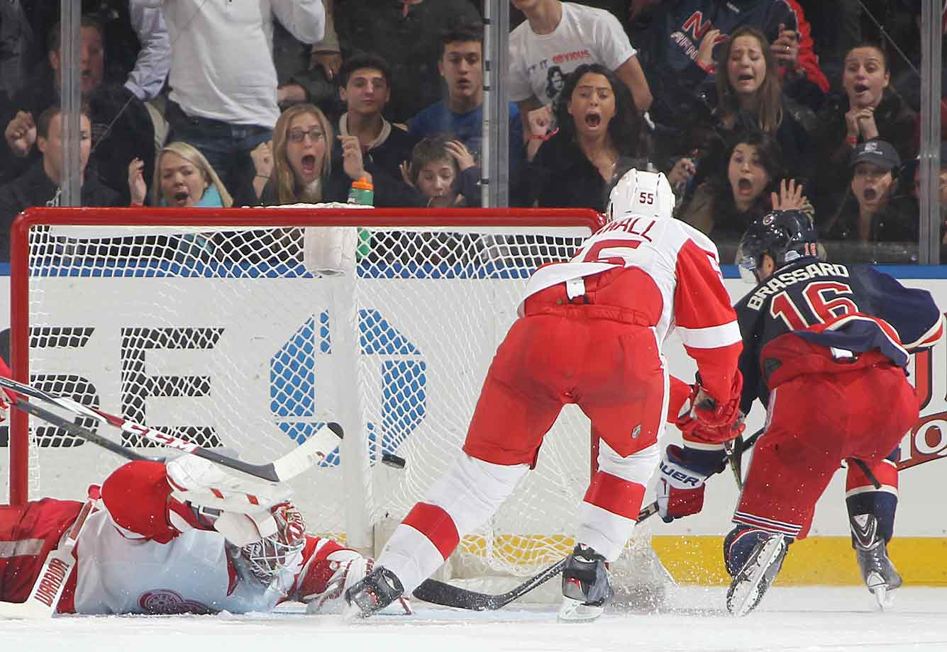 Derick Brassard of the Rangers delights the fans at Madison Square Garden by scoring the game-winning goal in overtime against Jonas Gustavsson of the Red Wings on November 5, 2014.