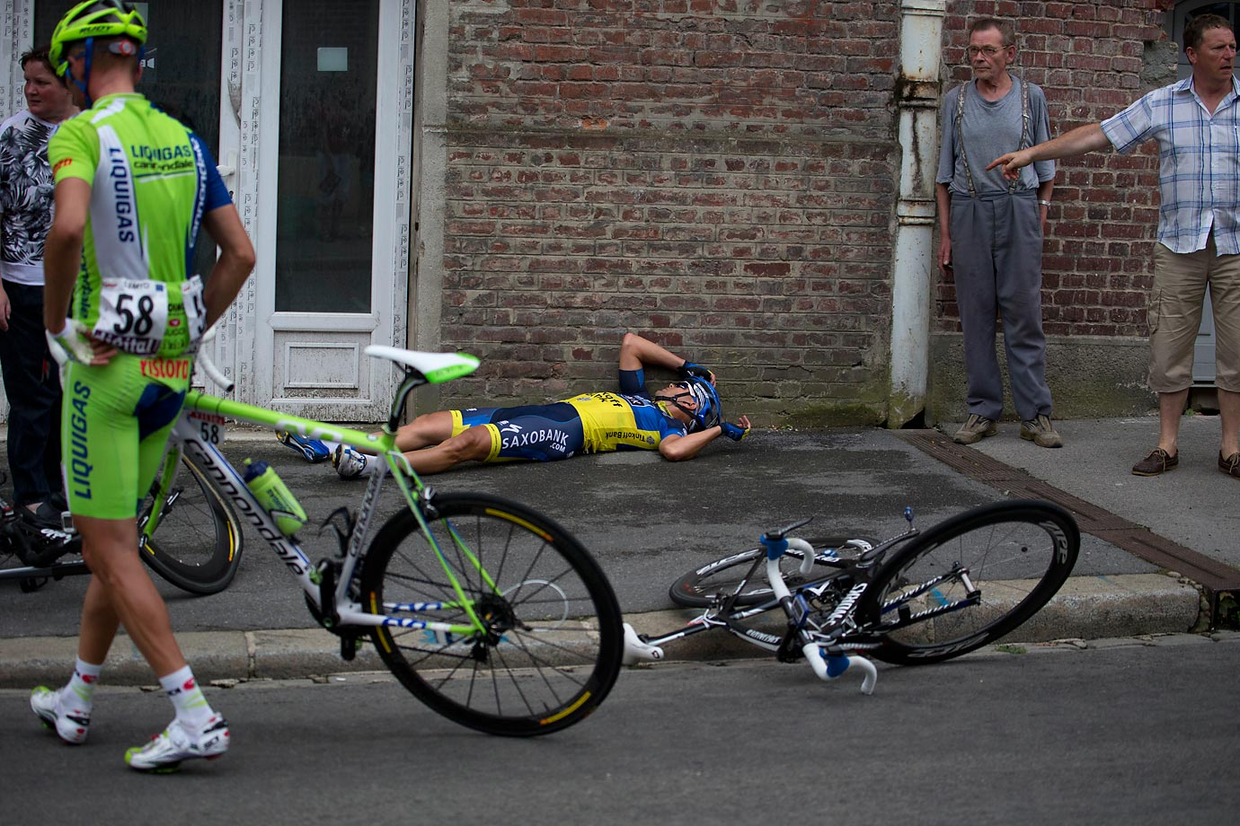 "Australian Jonathan Cantwell (supine) takes inventory after crashing with Poland's Sylvester Szmyd in Stage 5 of the 2012 Tour. After getting back on his bike and finishing the stage, Cantwell tweeted: ""Very sore with half of my right ass missing and ankle taking a hit from the gutter."""