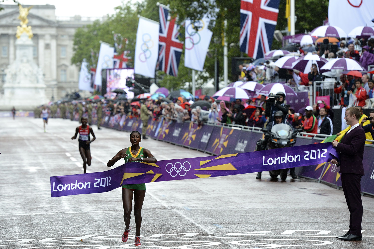 Gold medalist Tiki Gelana (C) crosses the finish line ahead of silver medallist Priscah Jeptoo (L) in the women's marathon at the 2012 London Olympic Games.