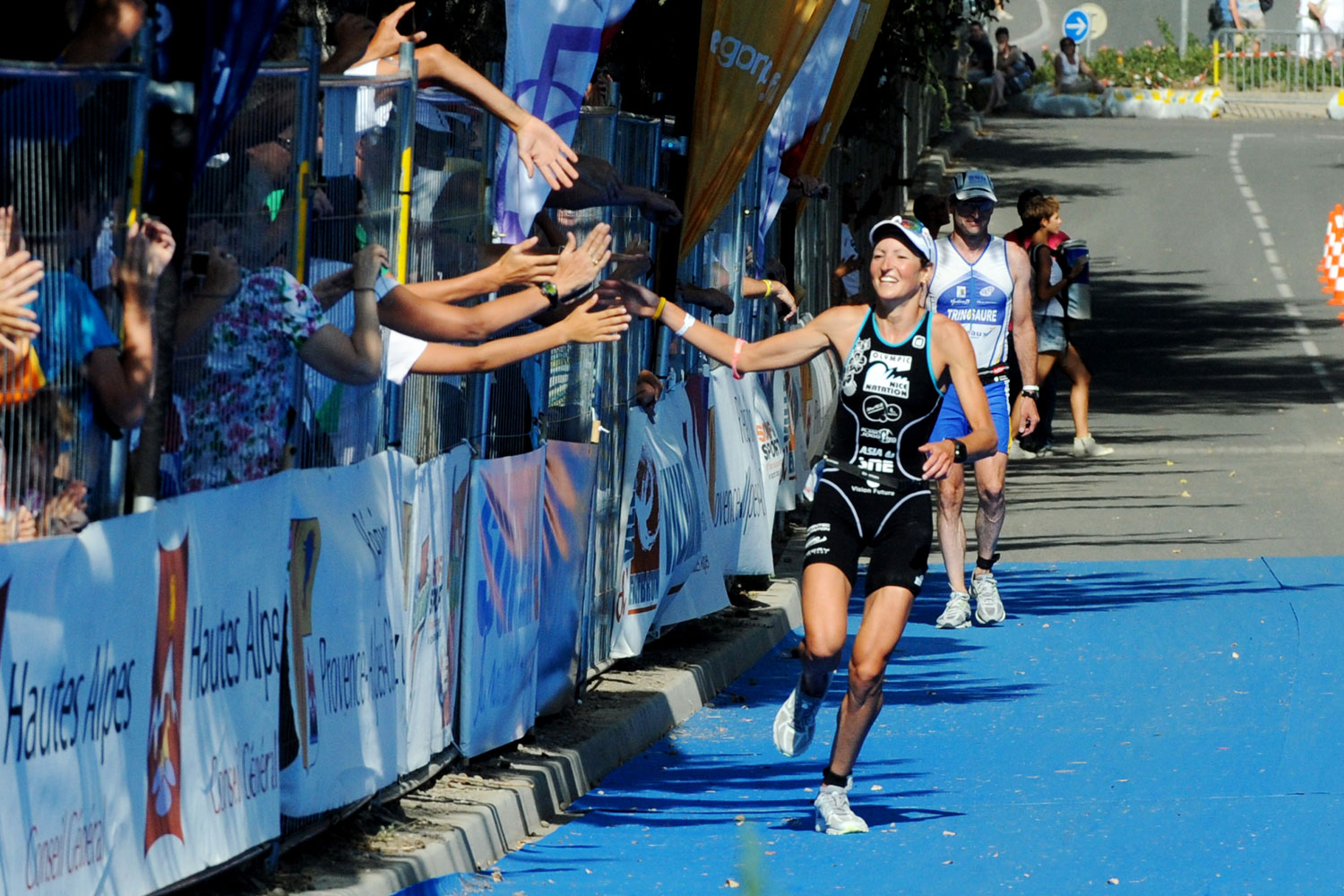 Jeanne Collange celebrates with supporters after crossing the finish line of the 29th edition of the Embrun Man triathlon in southeastern France.