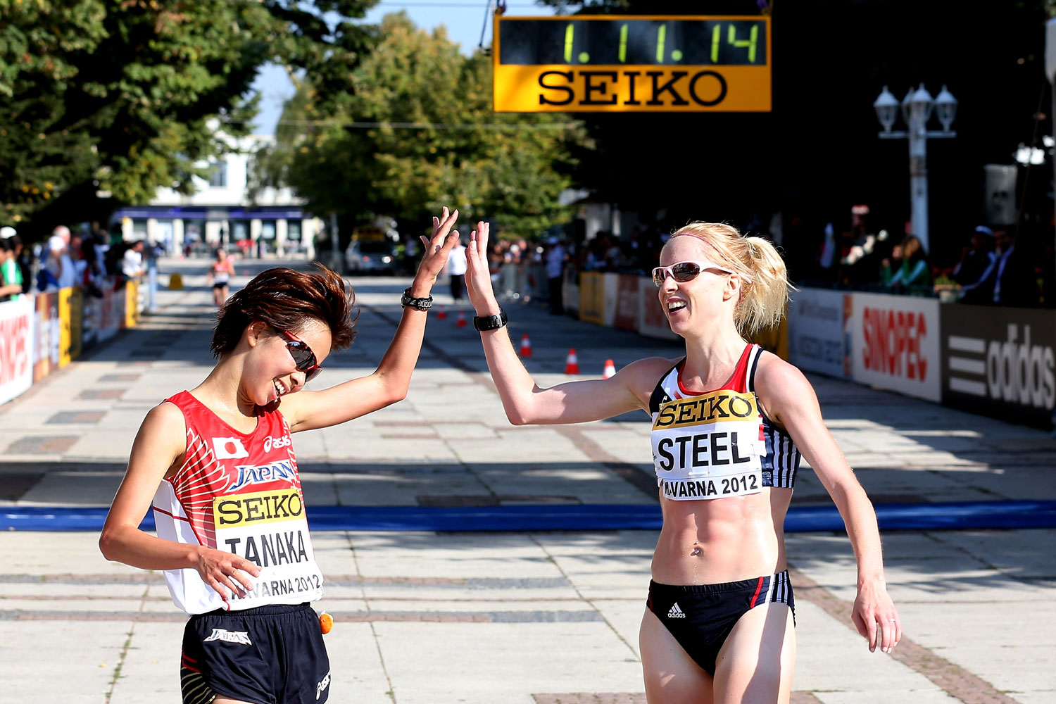 Gemma Steel of Great Britain crosses the finish line with Tomomi Tanaka of Japan during the 20th IAAF Women's World Half Marathon in Kavarna, Bulgaria.