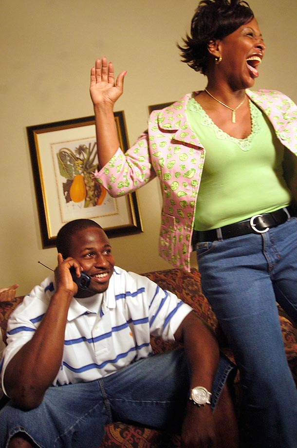 Auburn running back Carnell Williams talks on his cell phone with Tampa Bay Buccaneers coach Jon Gruden as his mother reacts to the news of Carnell being selected No. 5 by the Bucs in the 2005 draft.