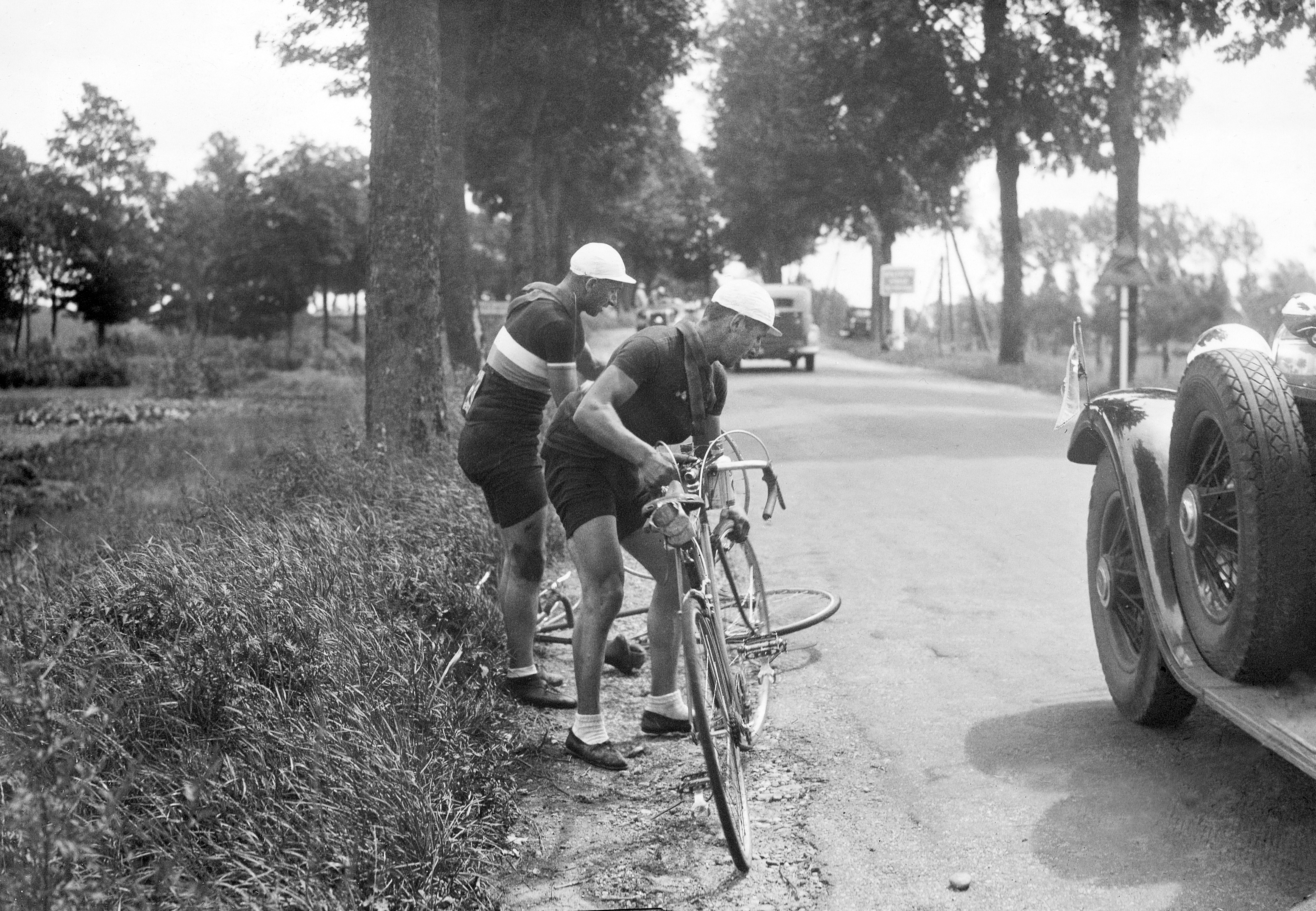 Racing cyclist Arsene Mersch of Luxembourg changes his wheel with Josy Krauss one's after a puncture during the fourth stage of the Tour de France, on July 10, 1934.